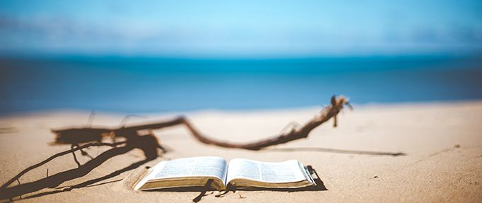 book in front of the ocean on the beach