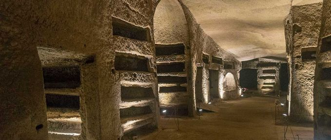 The tunnels of Naples Underground, featuring a hall with carved loculi (cavities).