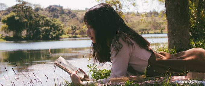 woman laying down reading a book