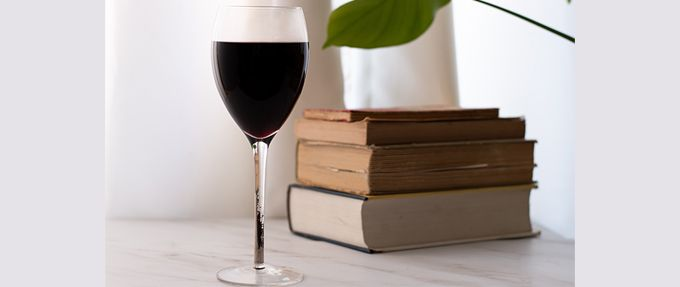 glass of wine and stack of books
