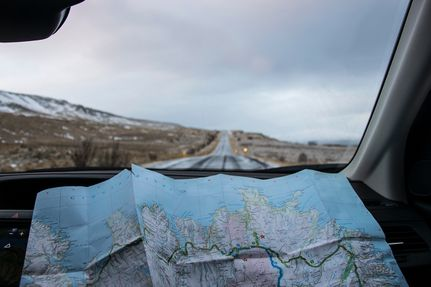 Unfolded map on a car dashboard with view of the road ahead