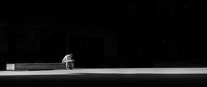 black and white photo of a man sitting and reading
