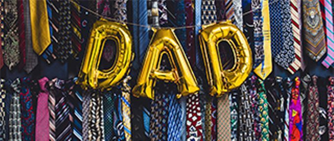 balloons spelling dad on background of ties