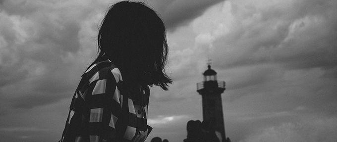 women staring at lighthouse