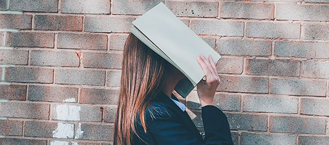 High school student with a book over her face.