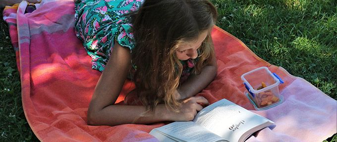 kid reading book in spring