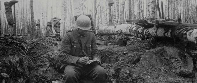 Soldier, writing a letter home amidst rubble from a battle in the woods.