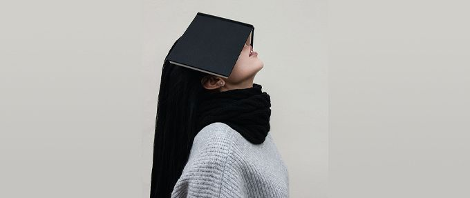 exasperated woman with book on her face