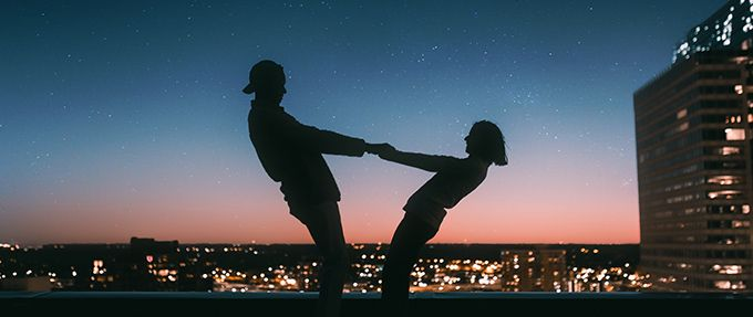 silhouetted couple dancing on roof at night
