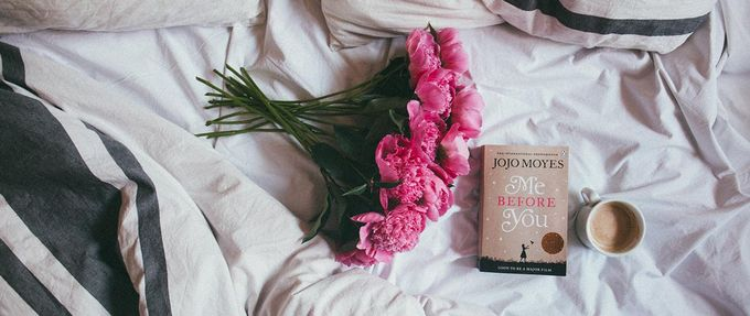 me before you, a romance book, on a bed with flowers