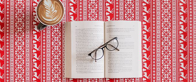 open book with glasses and coffee on a reindeer printed background