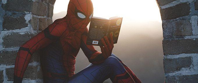 person in spiderman costume reading a book