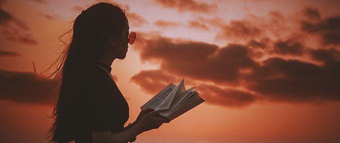 teen girl reading book on beach at sunset