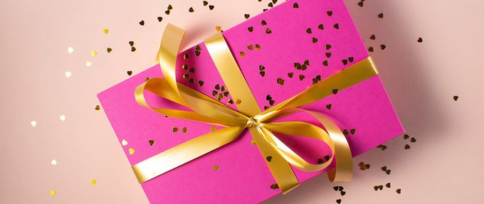 a valentine's day gift wrapped in a pink box and gold ribbon