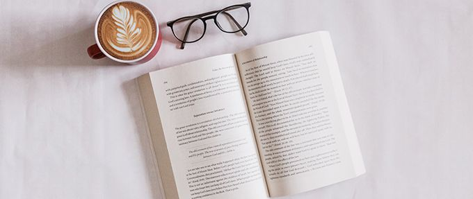 open book with latte and glasses