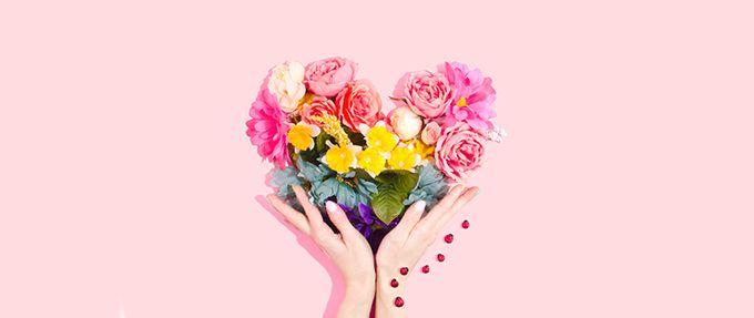 hands holding flowers shaped like heart