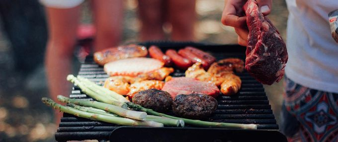 person grilling meat and vegetables
